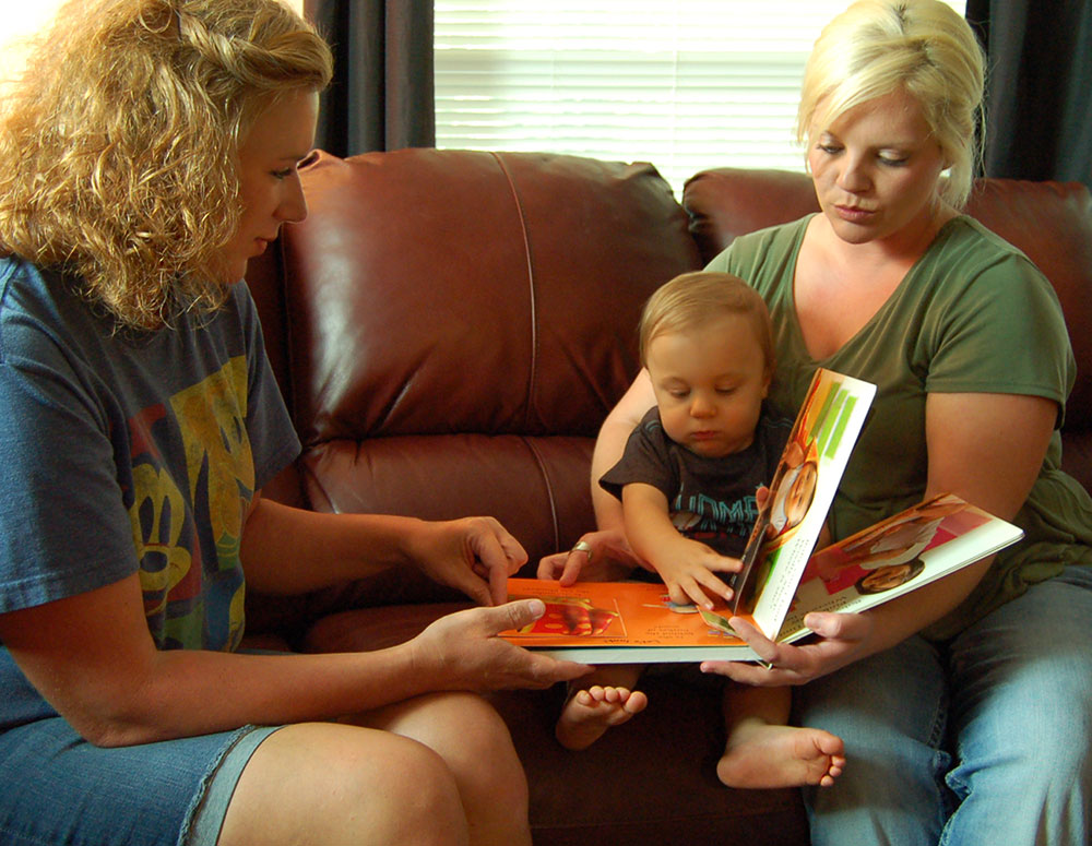 two women reading book with child